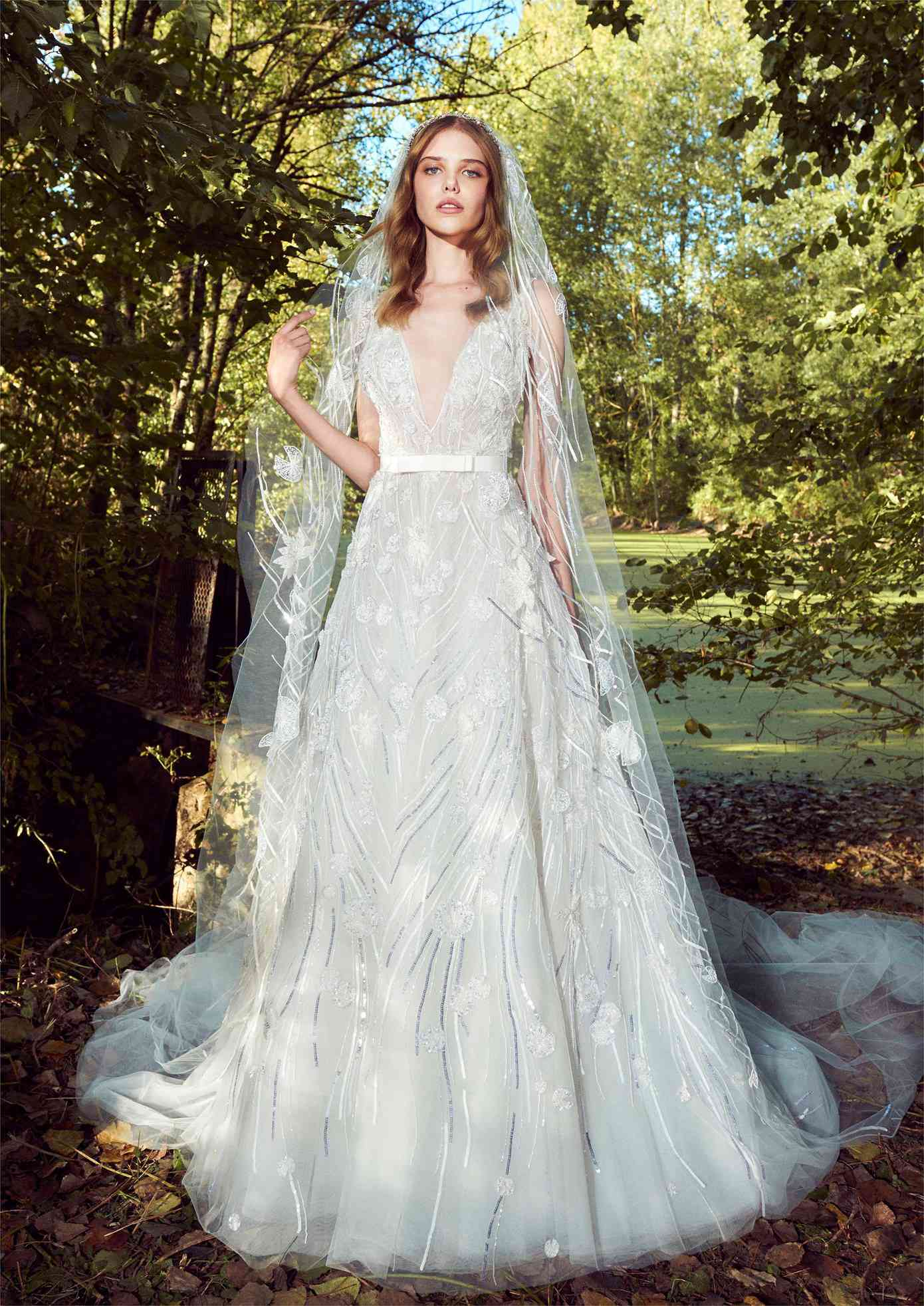 Model in a deep V-neck A-line gown with silver and clear beading and embroidery and a white bow waistband with a matching veil