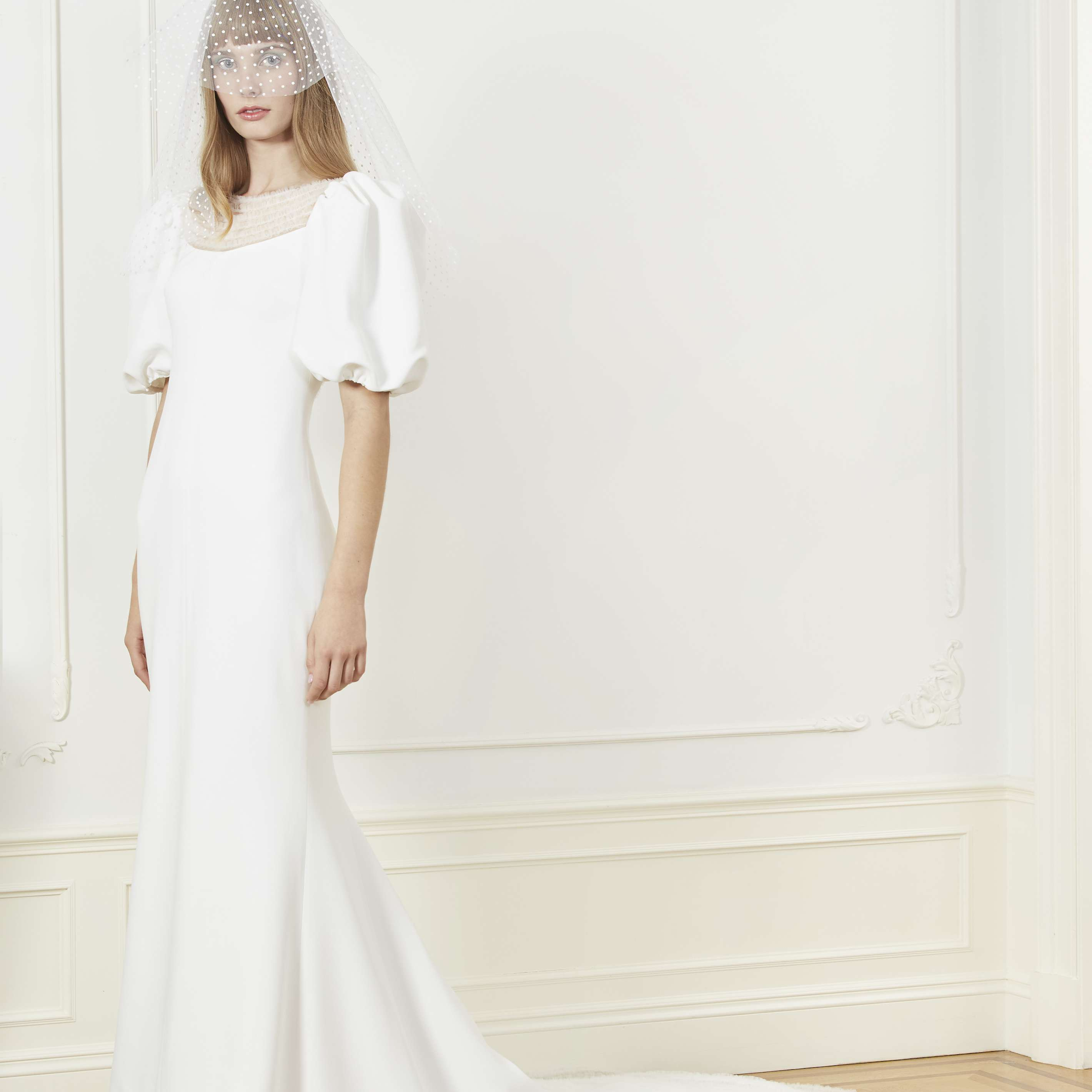 Model in fitted wedding dress with puff sleeves