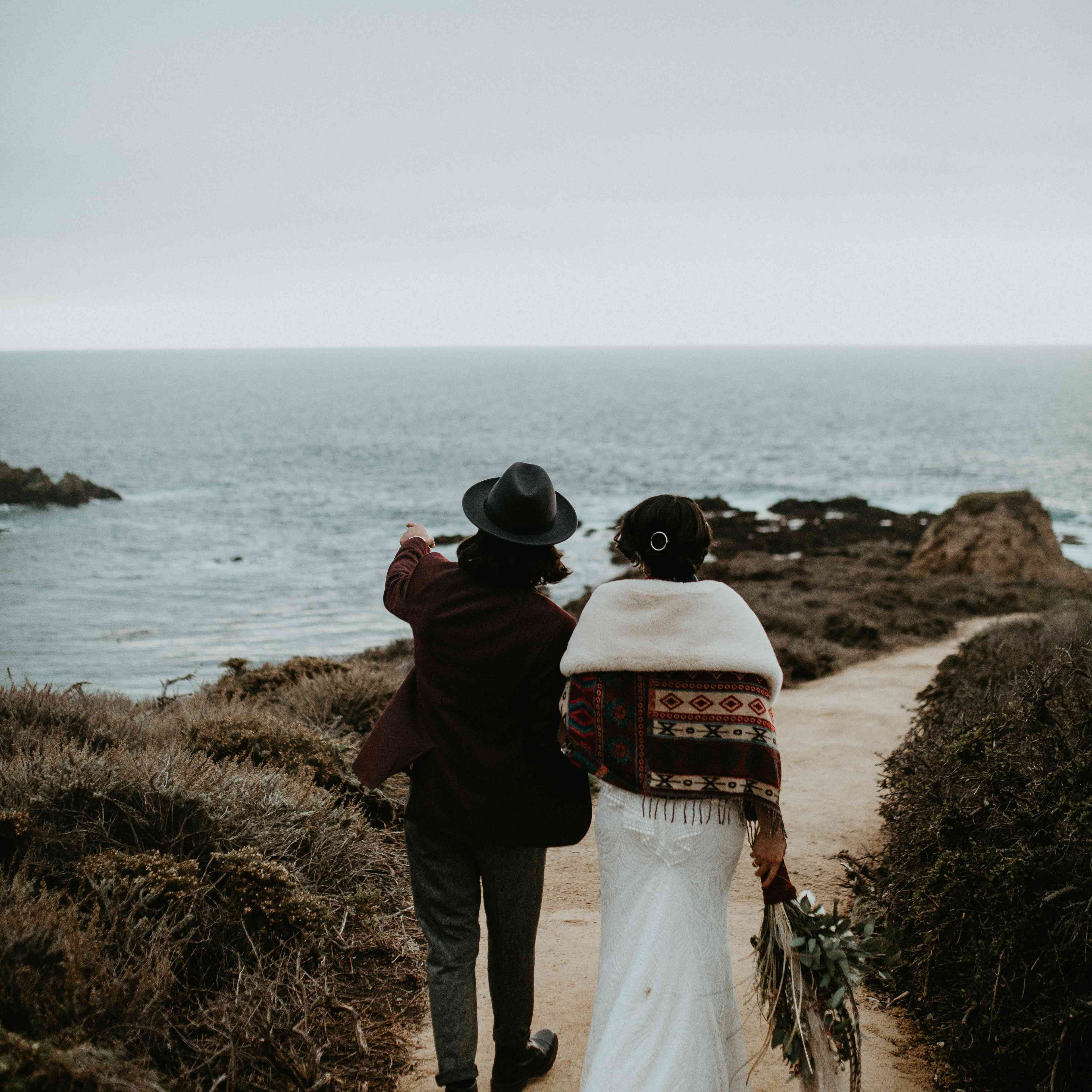 <p>bride in handmade blanket walking along the coast</p><br><br>