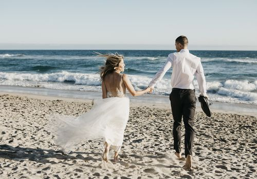 A couple in wedding attire hold hands and walk down the beach
