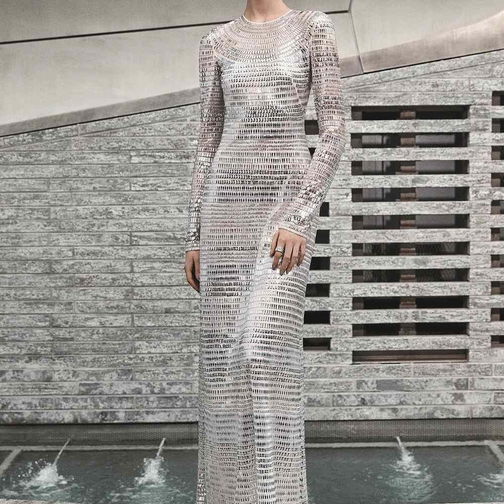 Model in long-sleeve silver sequined column gown