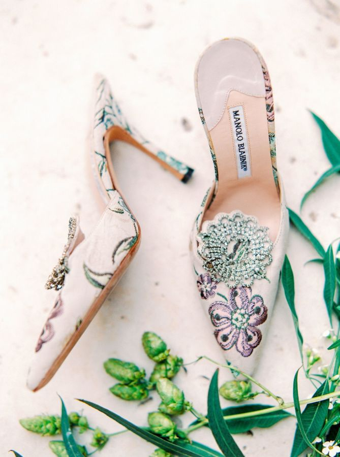A pair of floral-printed heels and greenery.