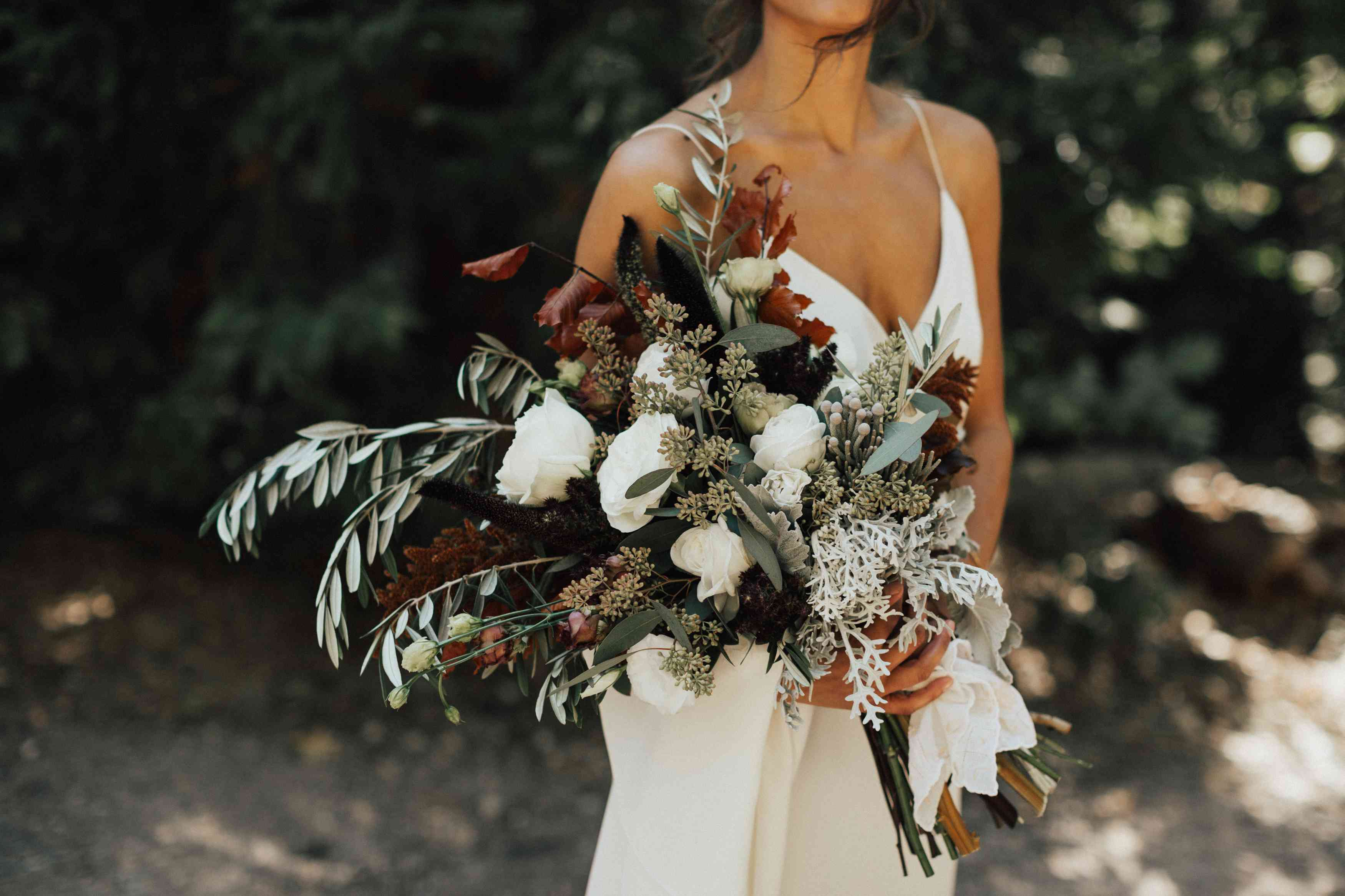 Bride's bouquet made from white roses, lush olive branches, eucalyptus, and fall leaves