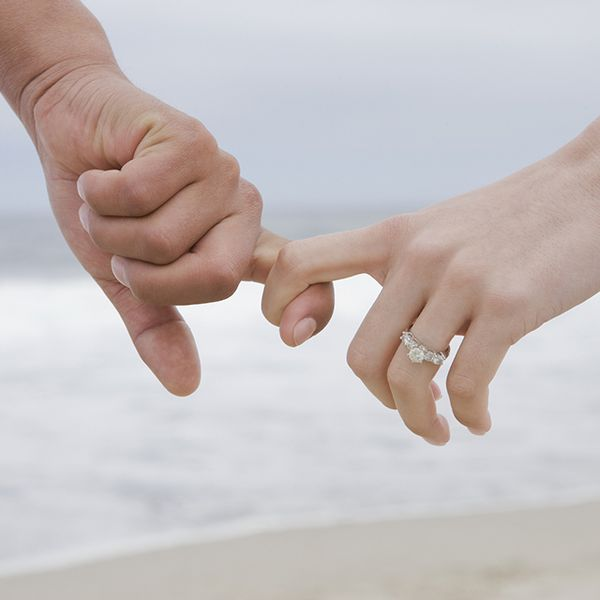 Couple holding fingers with engagement ring