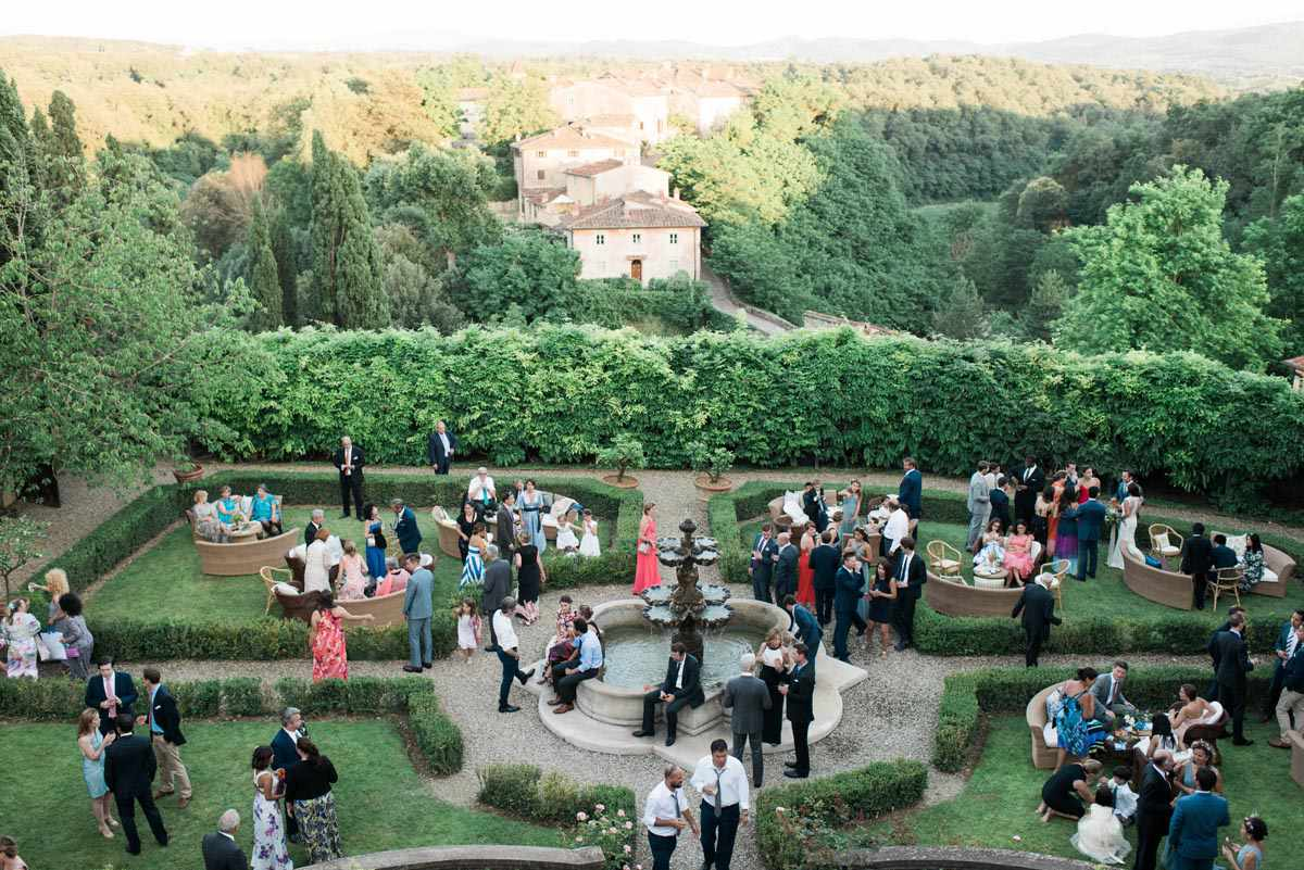 Aerial view of wedding guests on lawn in front of fountain