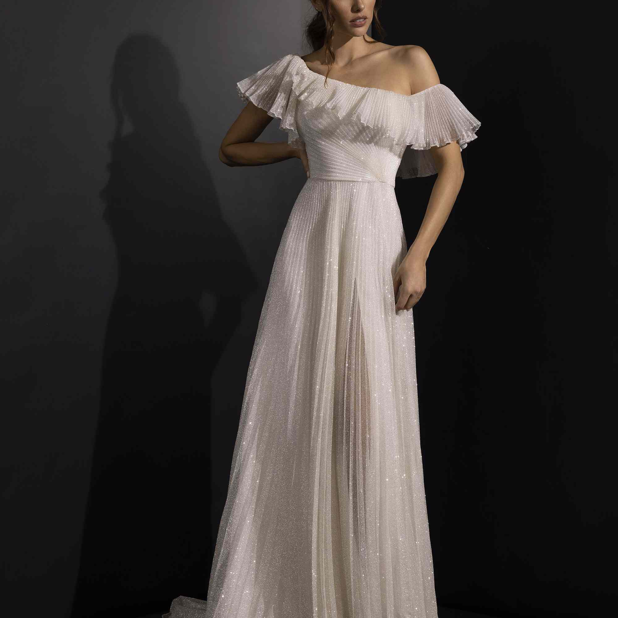 Model in asymmetrical off-the-shoulder dress with a ruffled neckline