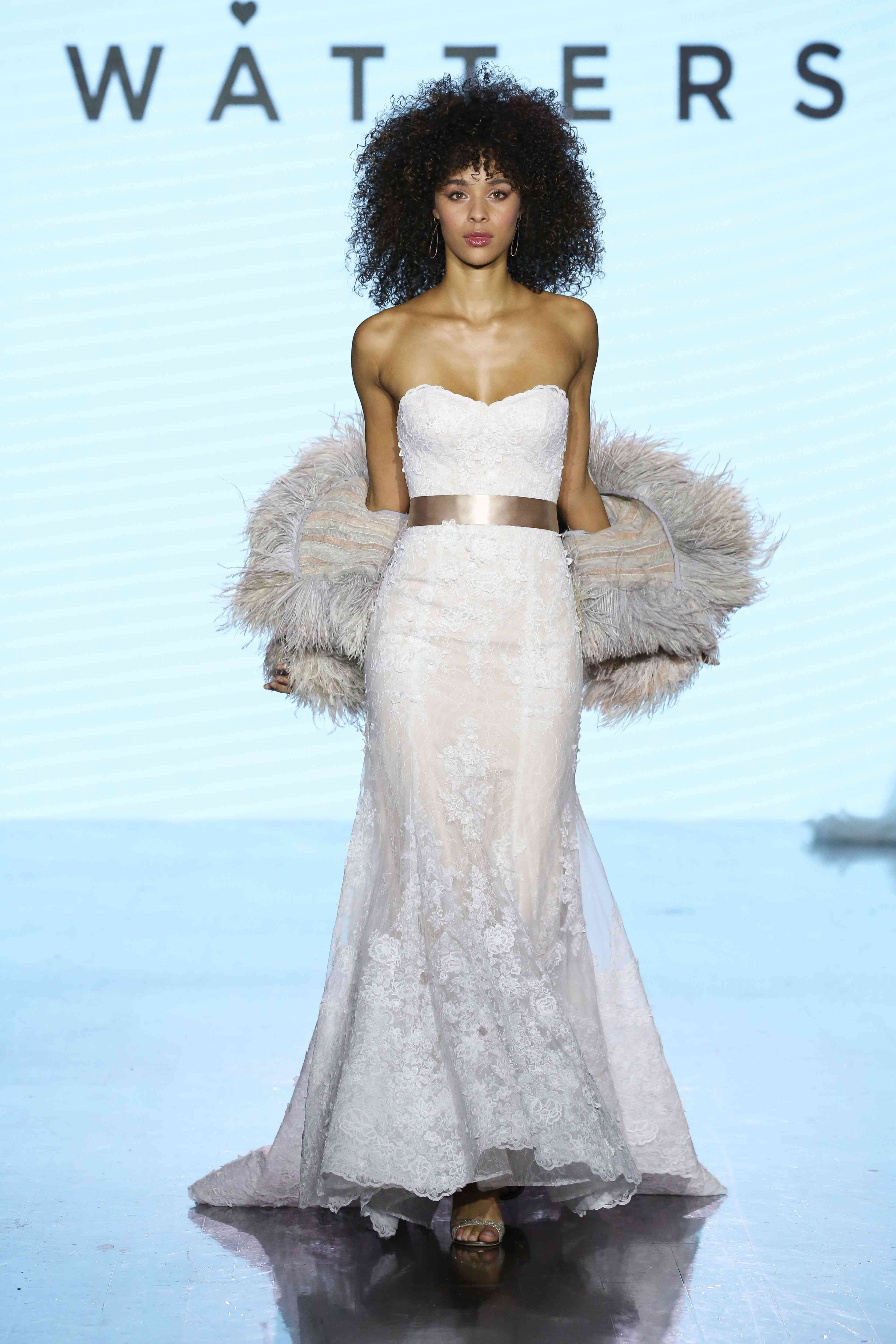 Model on runway in strapless sweetheart lace fit and flare gown with a gold satin belt