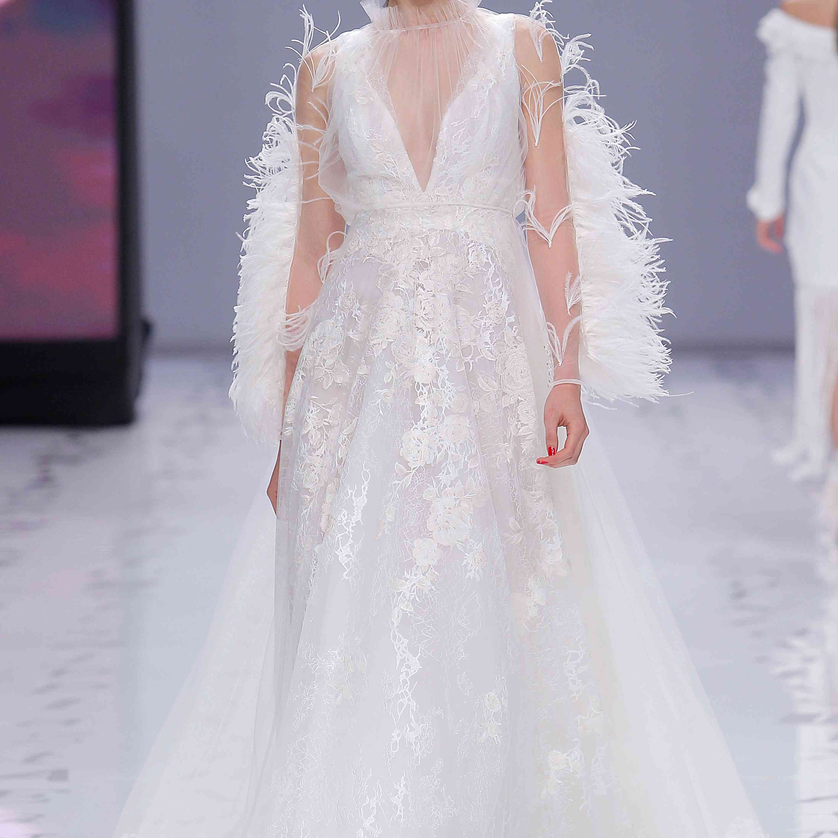 Model in embroidered tulle A-line dress with a gathered V-neckline on the front and back and sequin details and a tulle overdress with ostrich feathers
