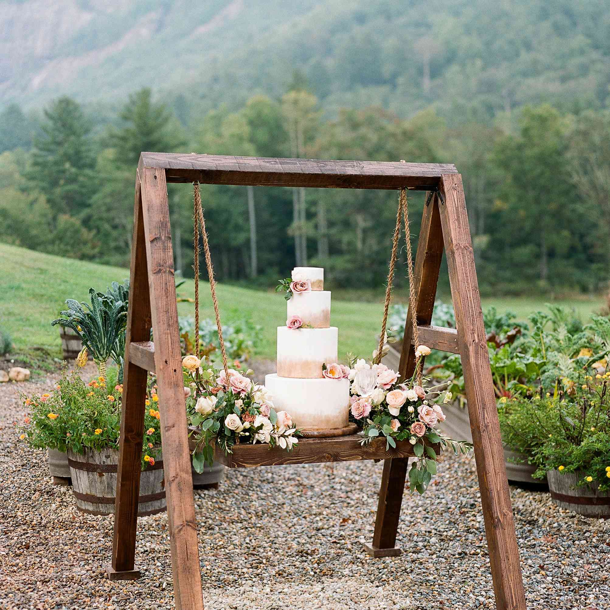 Four-tiered white wedding cake with brushed gold accents displayed on a wooden swing