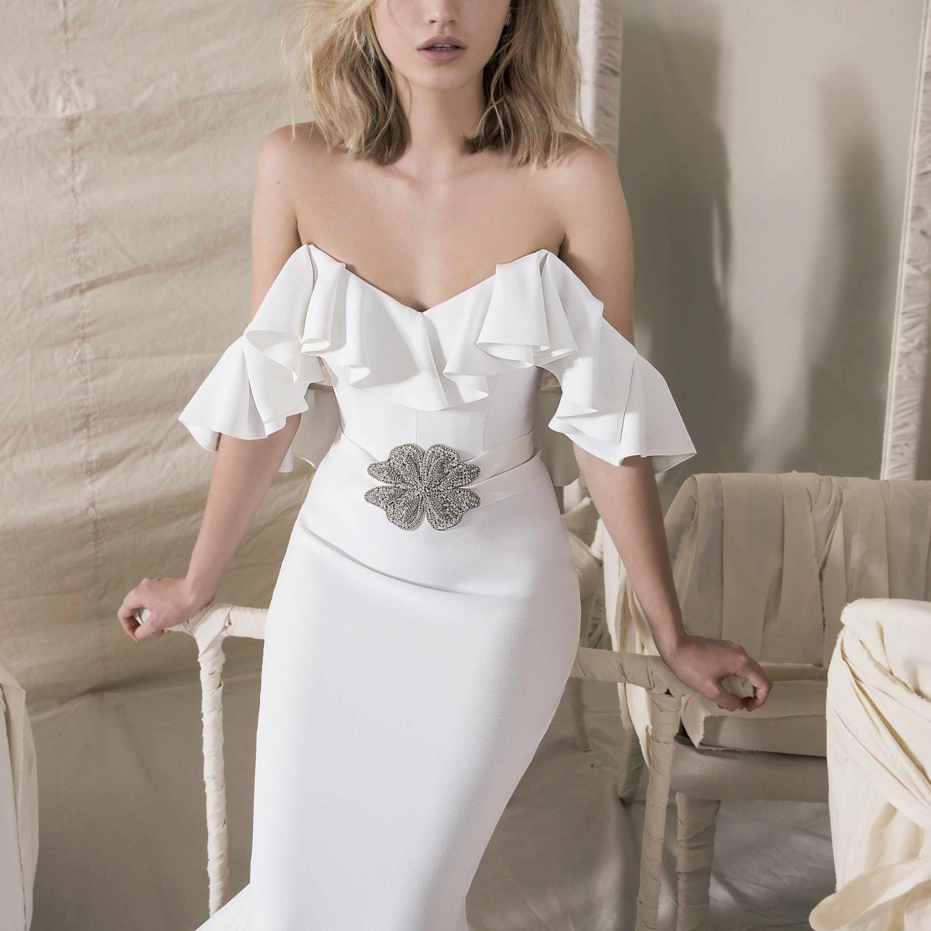Model in ruffled off-the-shoulder mermaid gown with brooch on waist