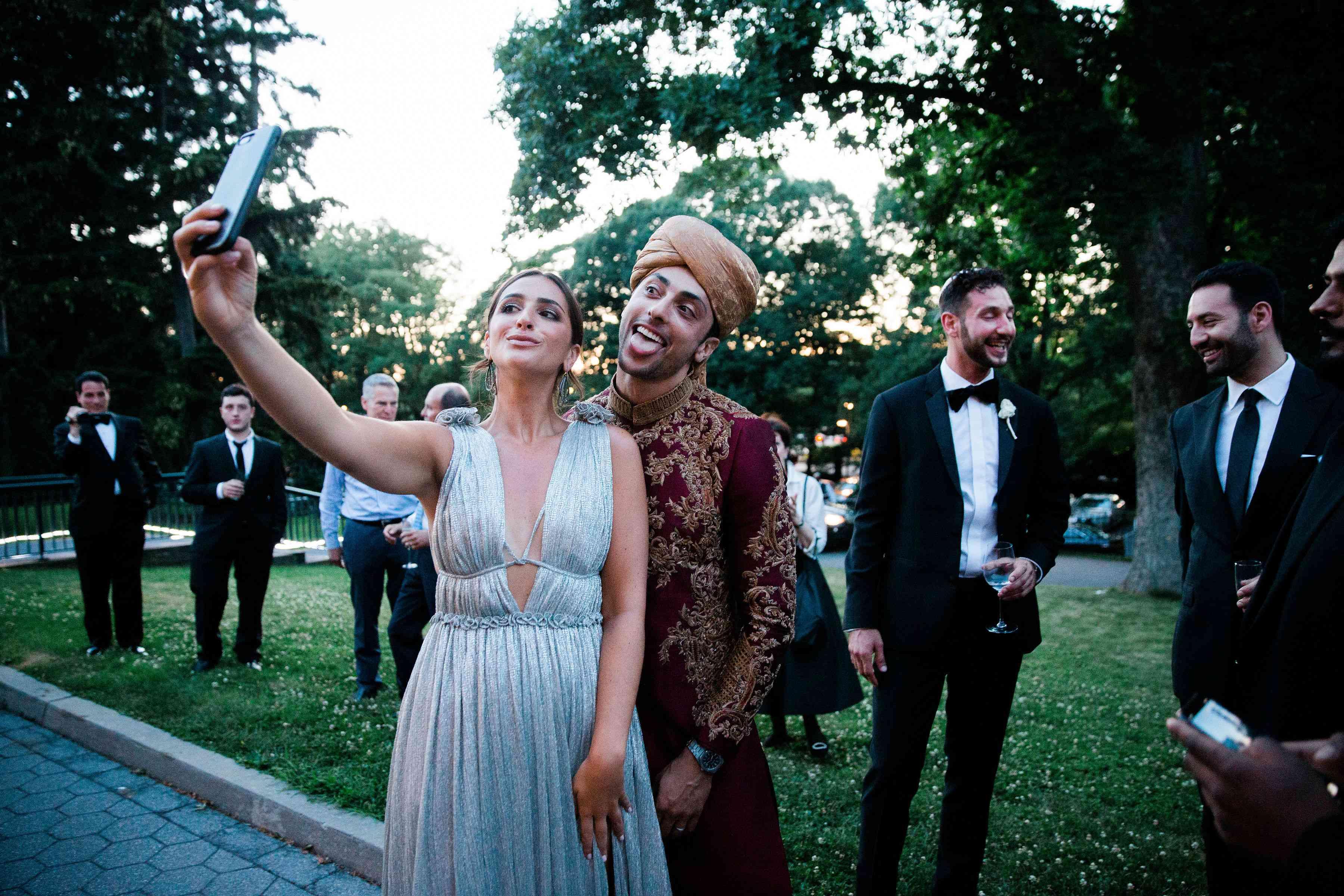 Groom and bridesmaid taking selfie