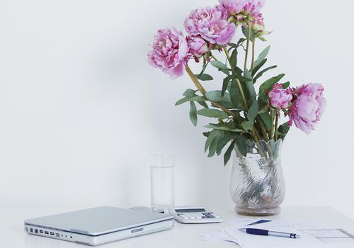 <p>Laptop and peony bouquet on desk</p>