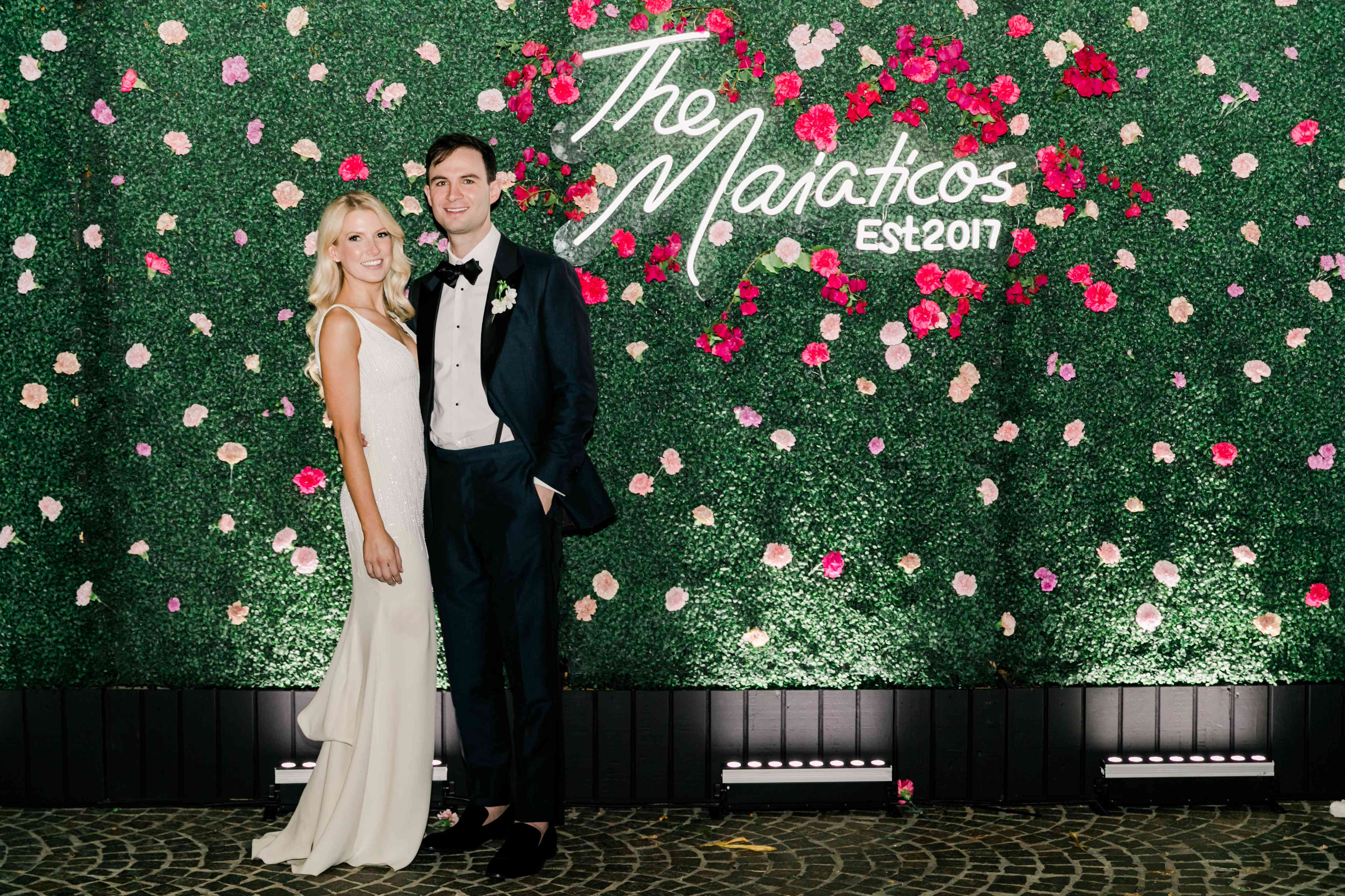 Newlyweds in front of flower wall with neon sign of their name