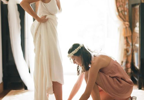Bridesmaid assists bride with her heels on the wedding day