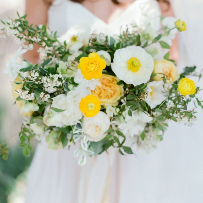 Bride holding white and yellow bouquet of ranunculus, garden roses, Icelandic white poppy, jasmine vine, white garden roses, and varigated mini pittosporum