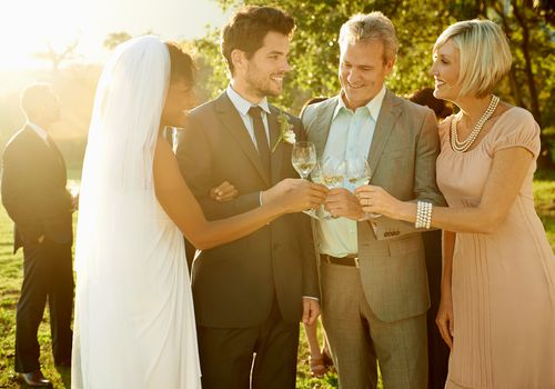 a newlywed couple standing with the groom's parents after the wedding ceremony