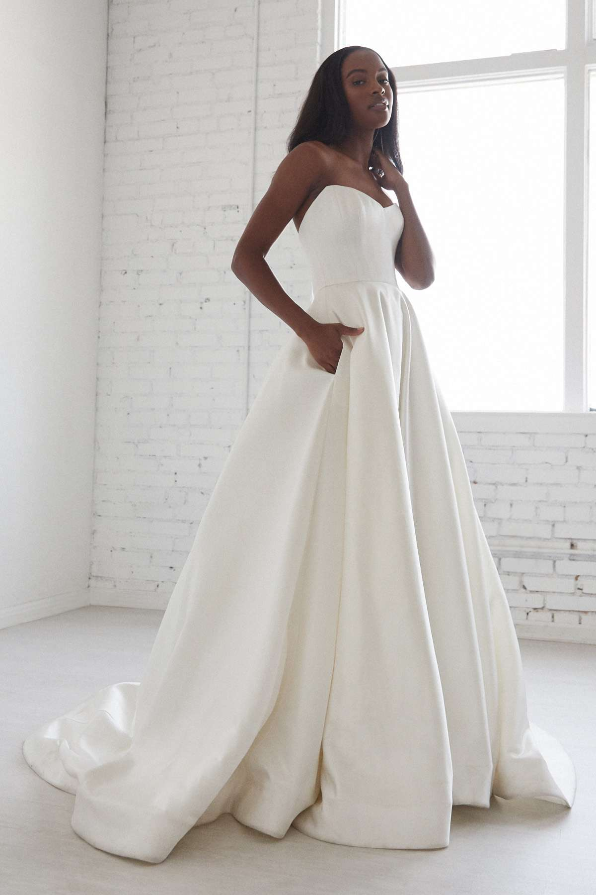 Model in strapless satin ballgown with skirt pockets
