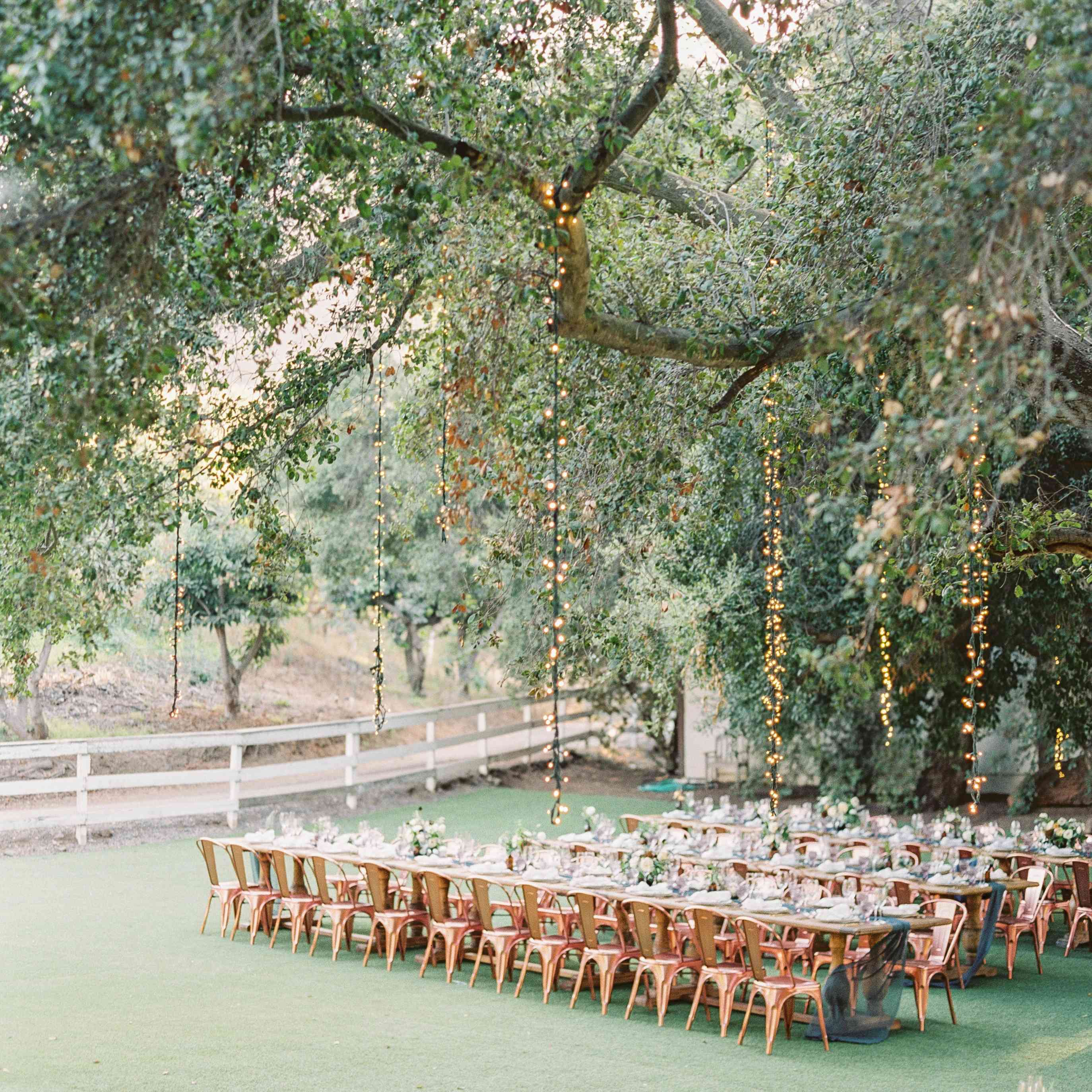 long reception tables copper chairs string lights