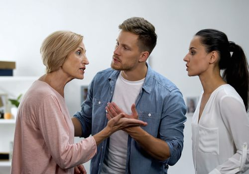Young man settling conflict between mother and wife