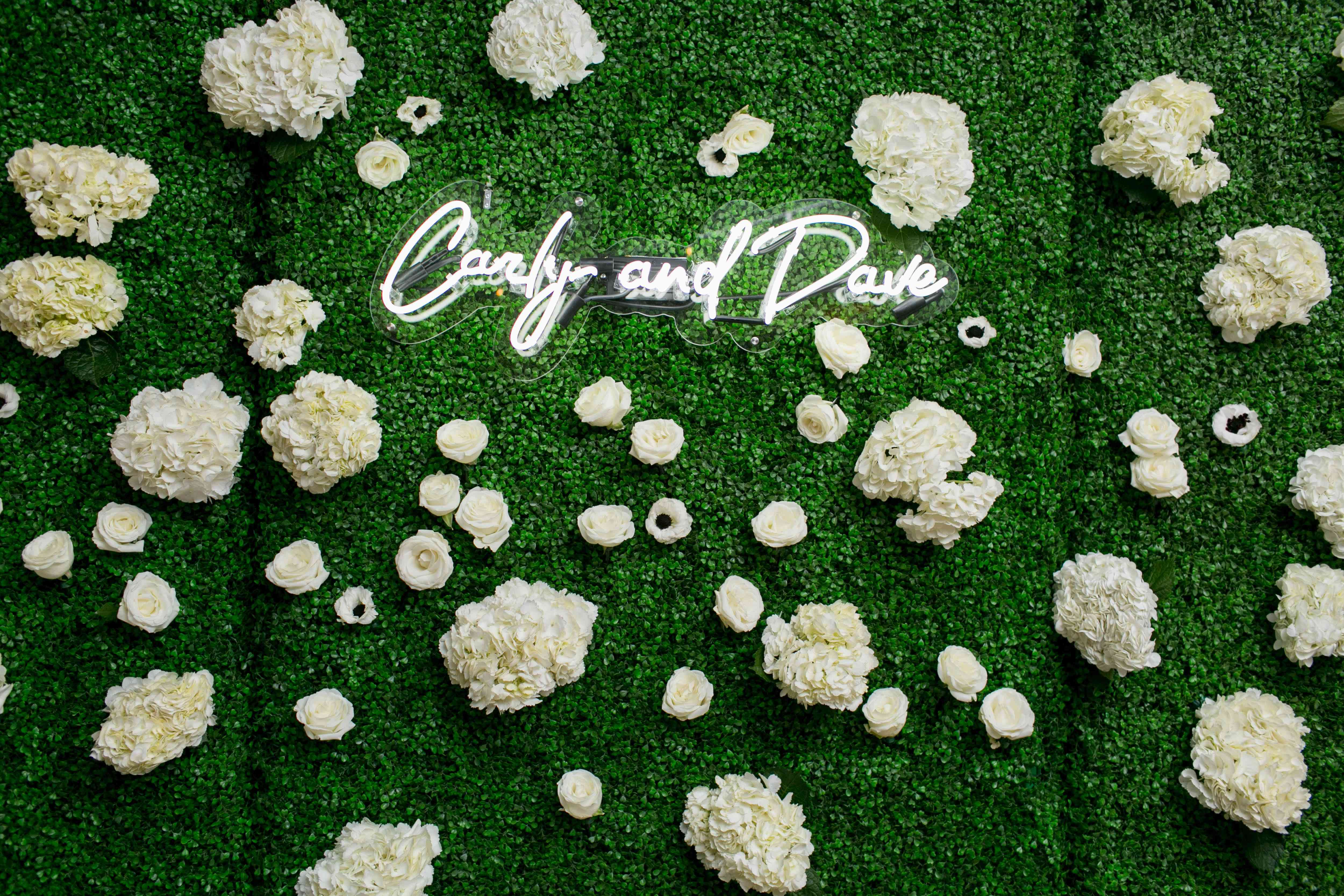 Neon sign on floral wall of greenery and hydrangeas