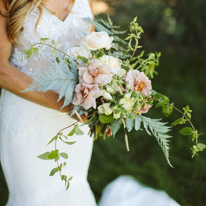Bride holding a small bouquet of ferns and light pink roses