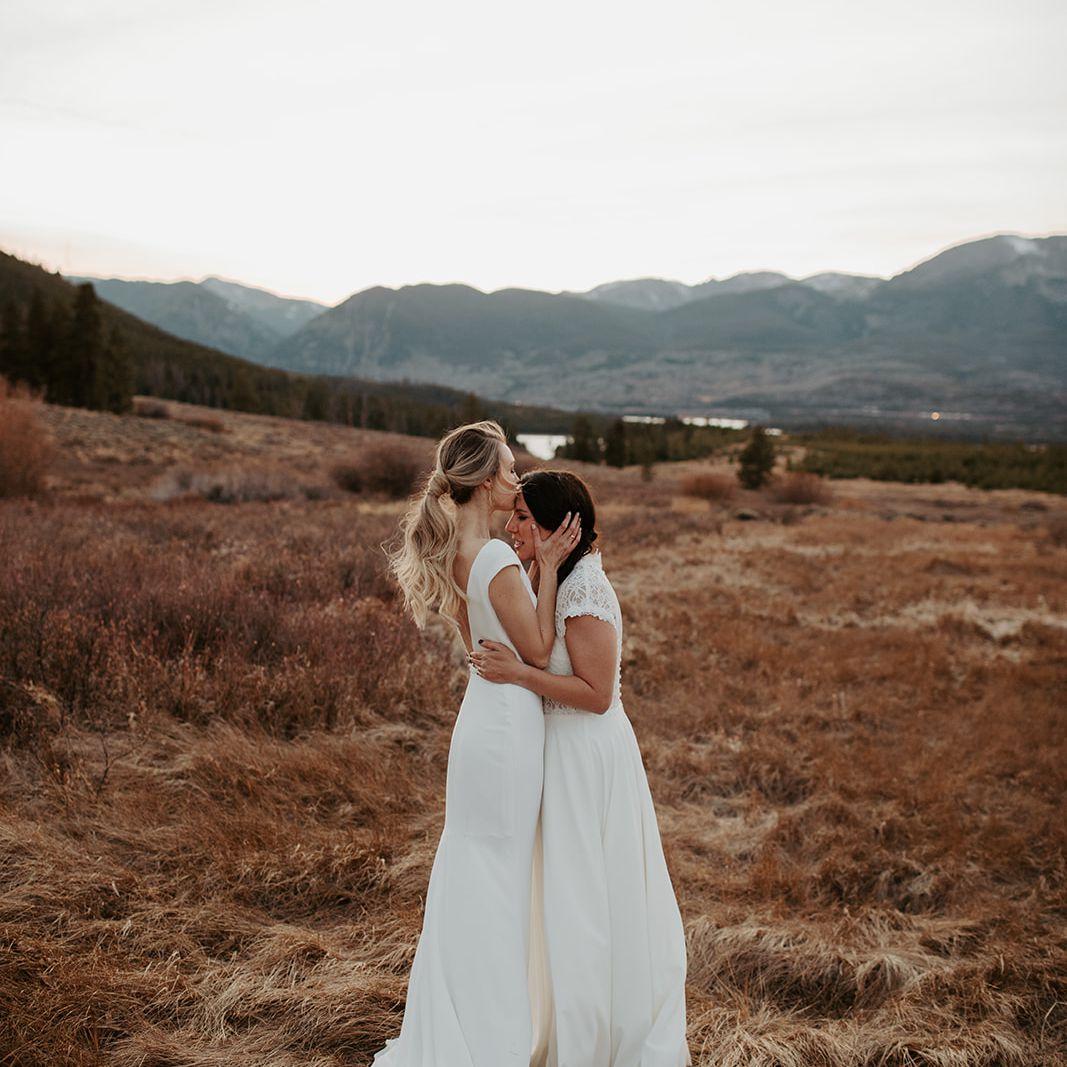 Brides embrace before ceremony