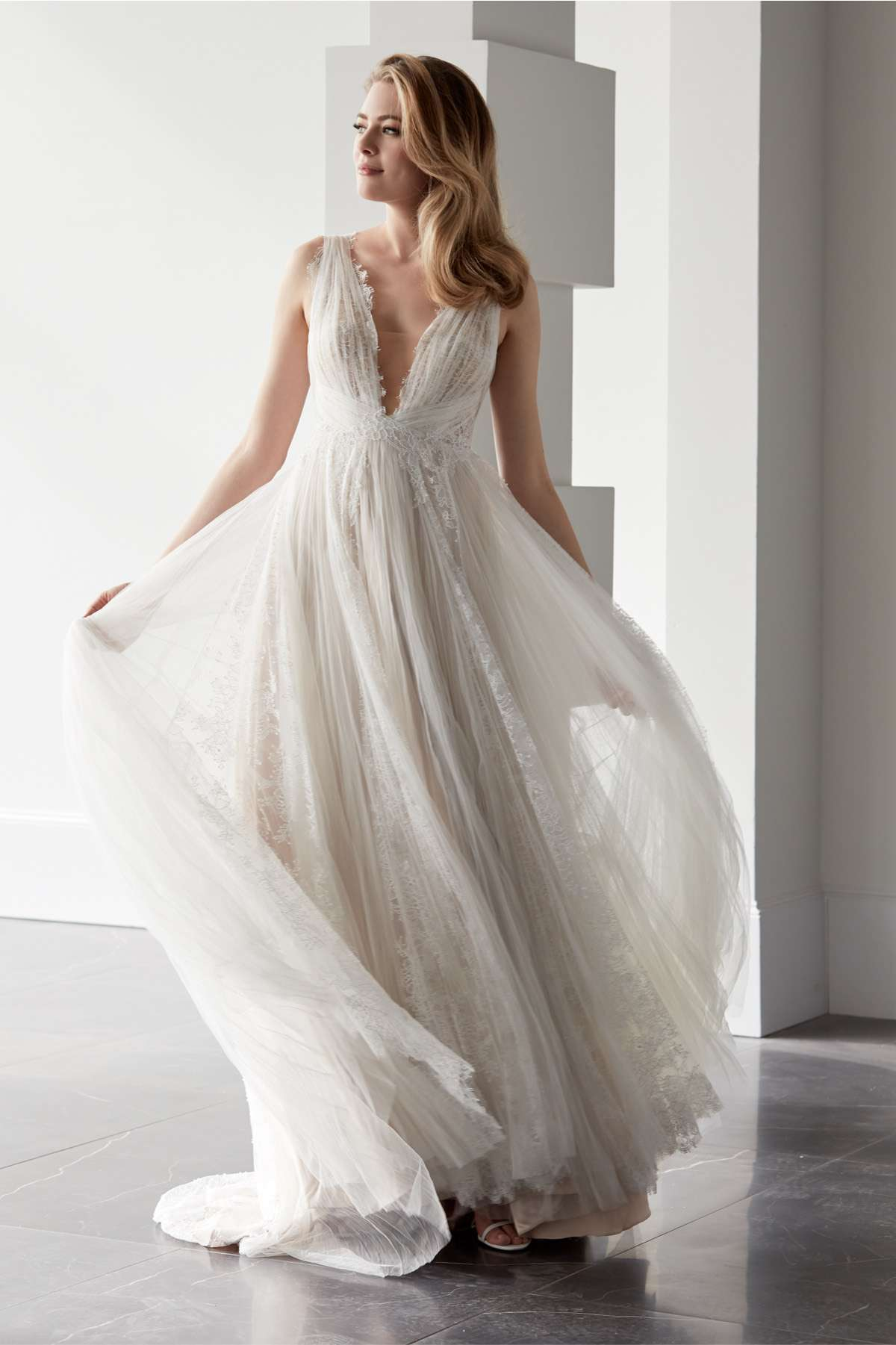Model in sleeveless A-line gown with lace and a deep illusion neckline