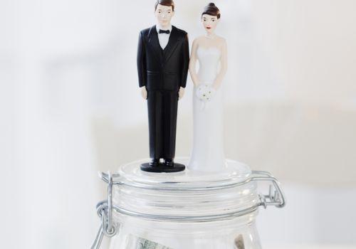 Groom and bride figurines atop mason jar full of dollars