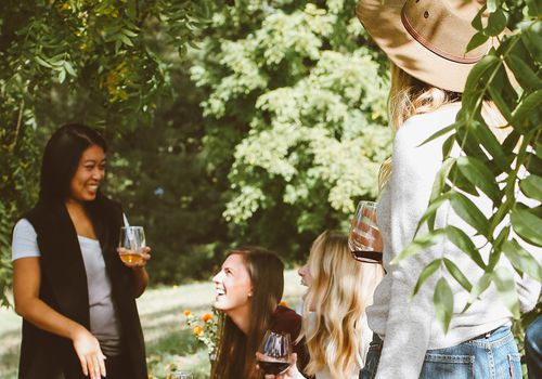 group of friends outdoors with wine
