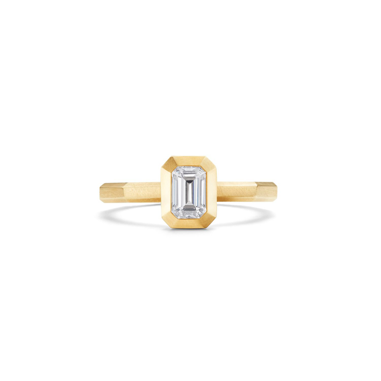Bezel diamond engagement ring with yellow gold band on a white background.