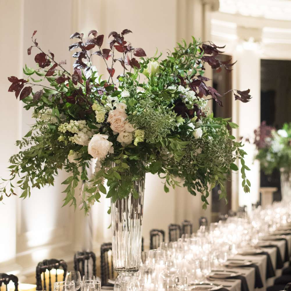 tall floral centerpieces of lush greenery and peonies