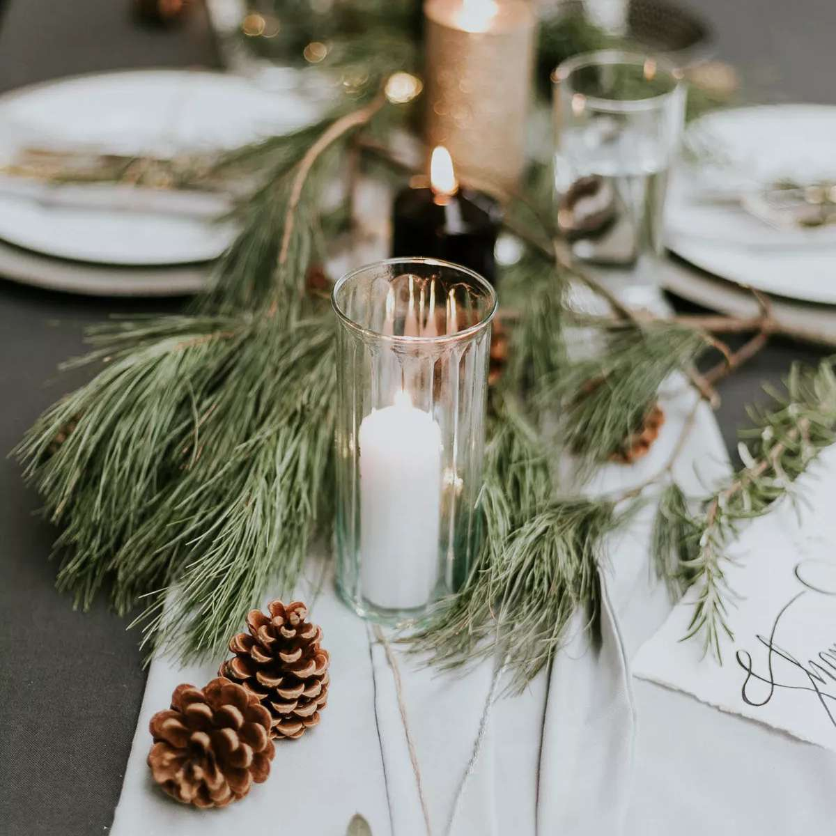Table decor featuring greenery, candles, and pine cones