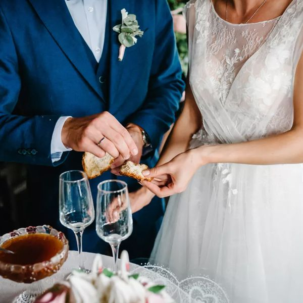 bride and groom sharing a sweet bread