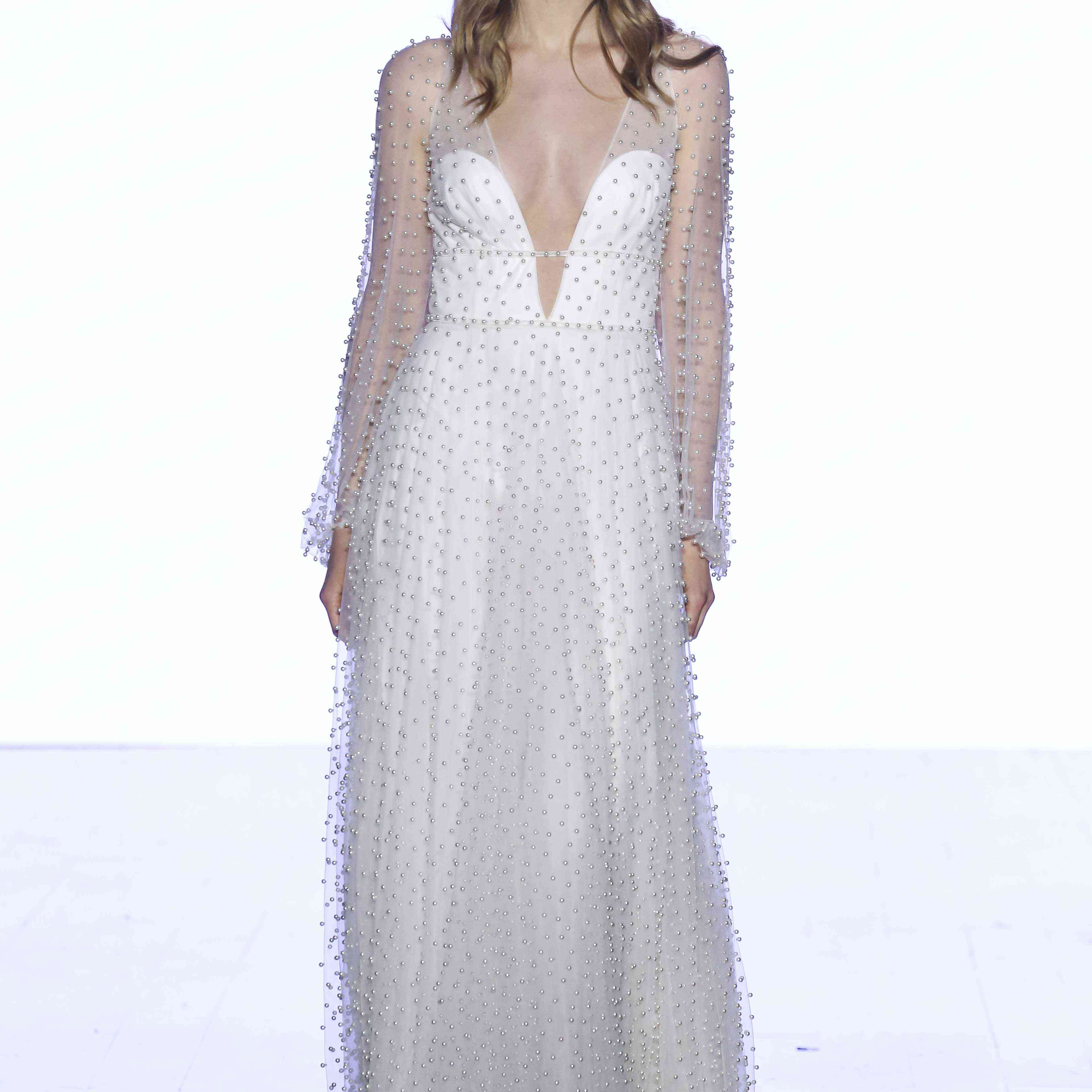 Model in long-sleeve V-neck illusion tulle gown with allover sparkling stones1