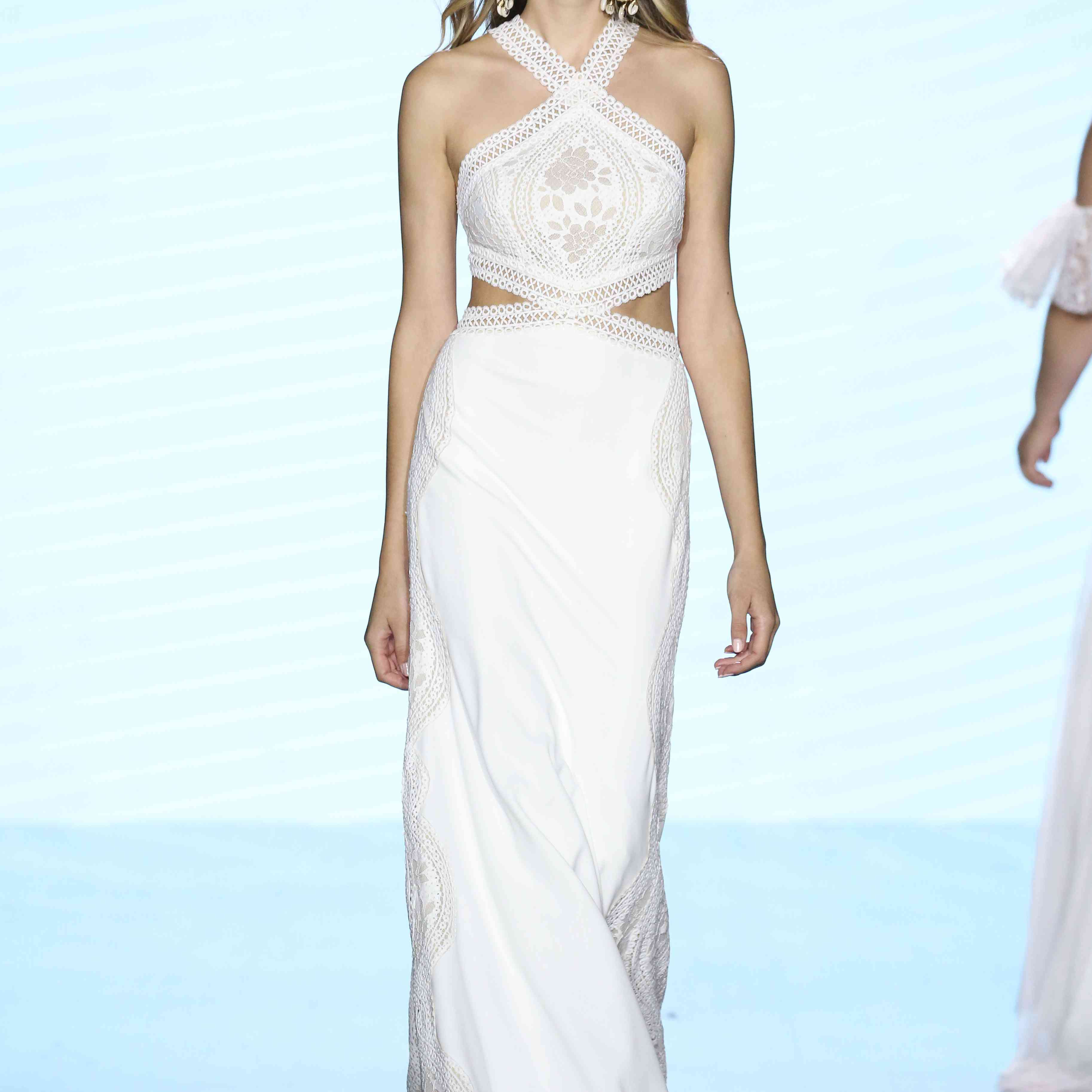 Model in halter wedding dress with side cutouts and lace panels