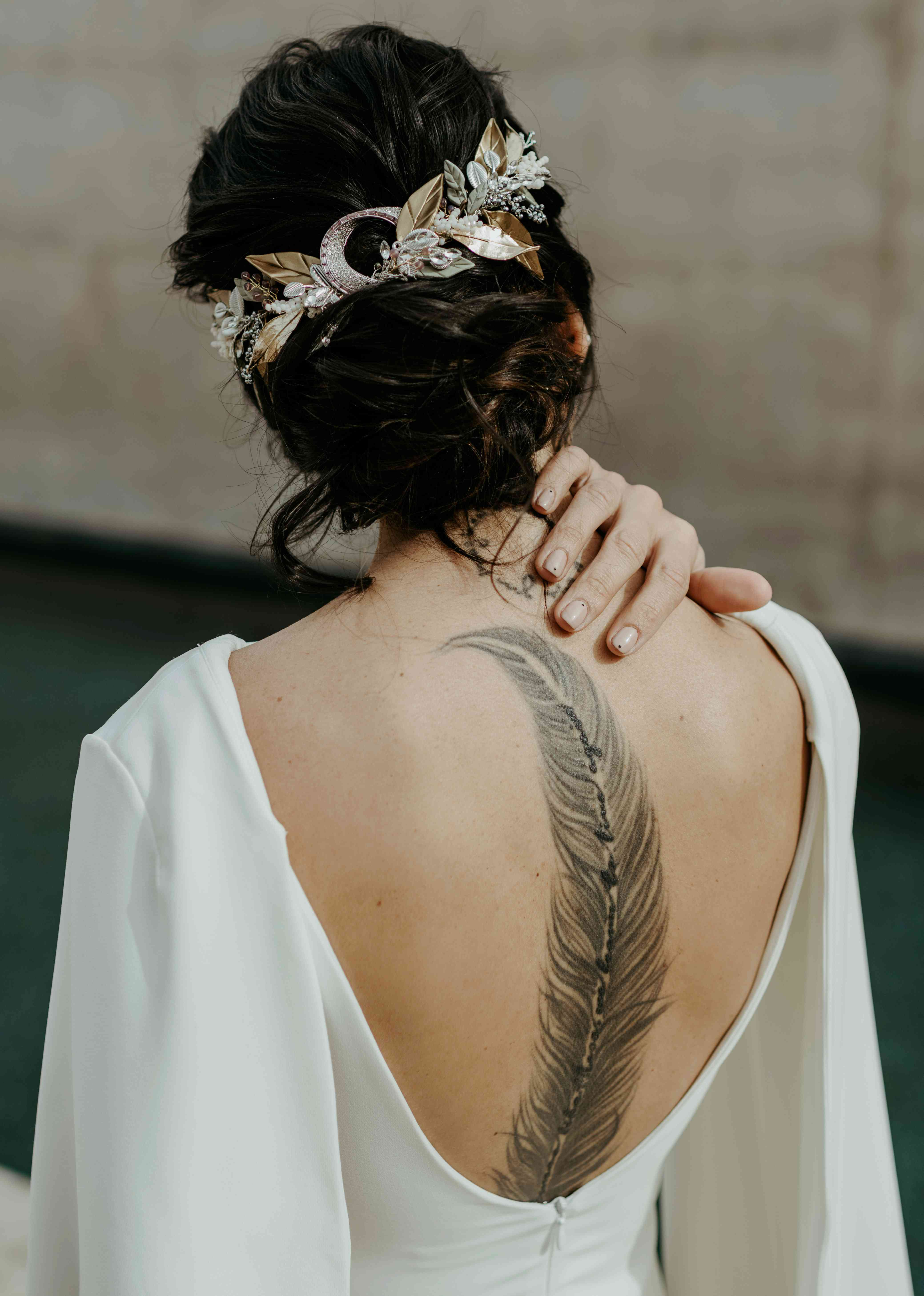 Bride showing off back tattoo and messy chignon