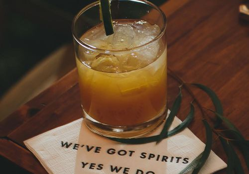 "A cocktail on a napkin that reads ""We've got spirits, yes we do"""