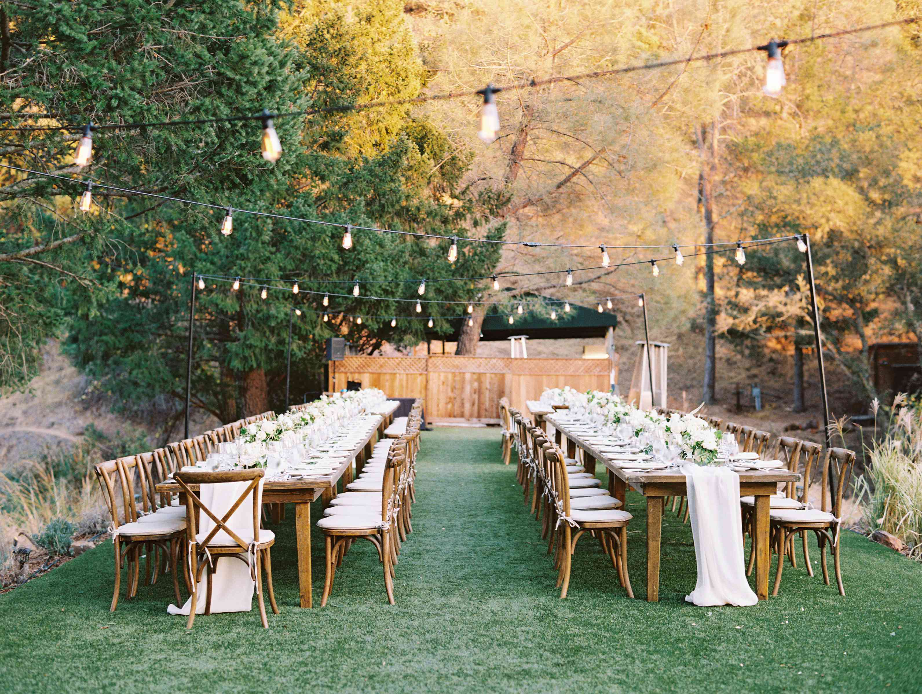 String lights above tables at outdoor reception