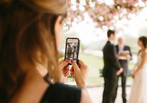 Guest taking photo of bride and groom on phone