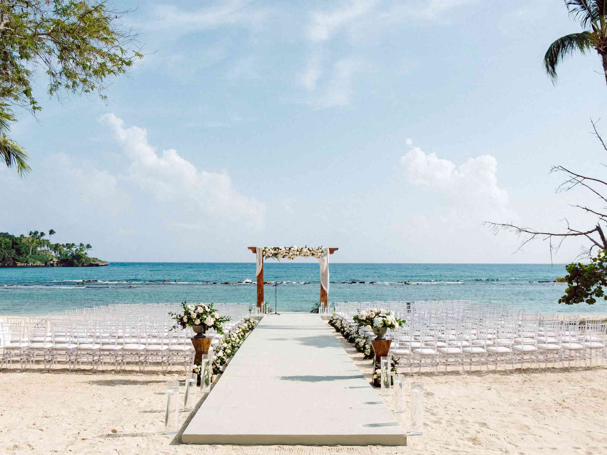 A beach ceremony with an elevated aisle lined with floral arrangements
