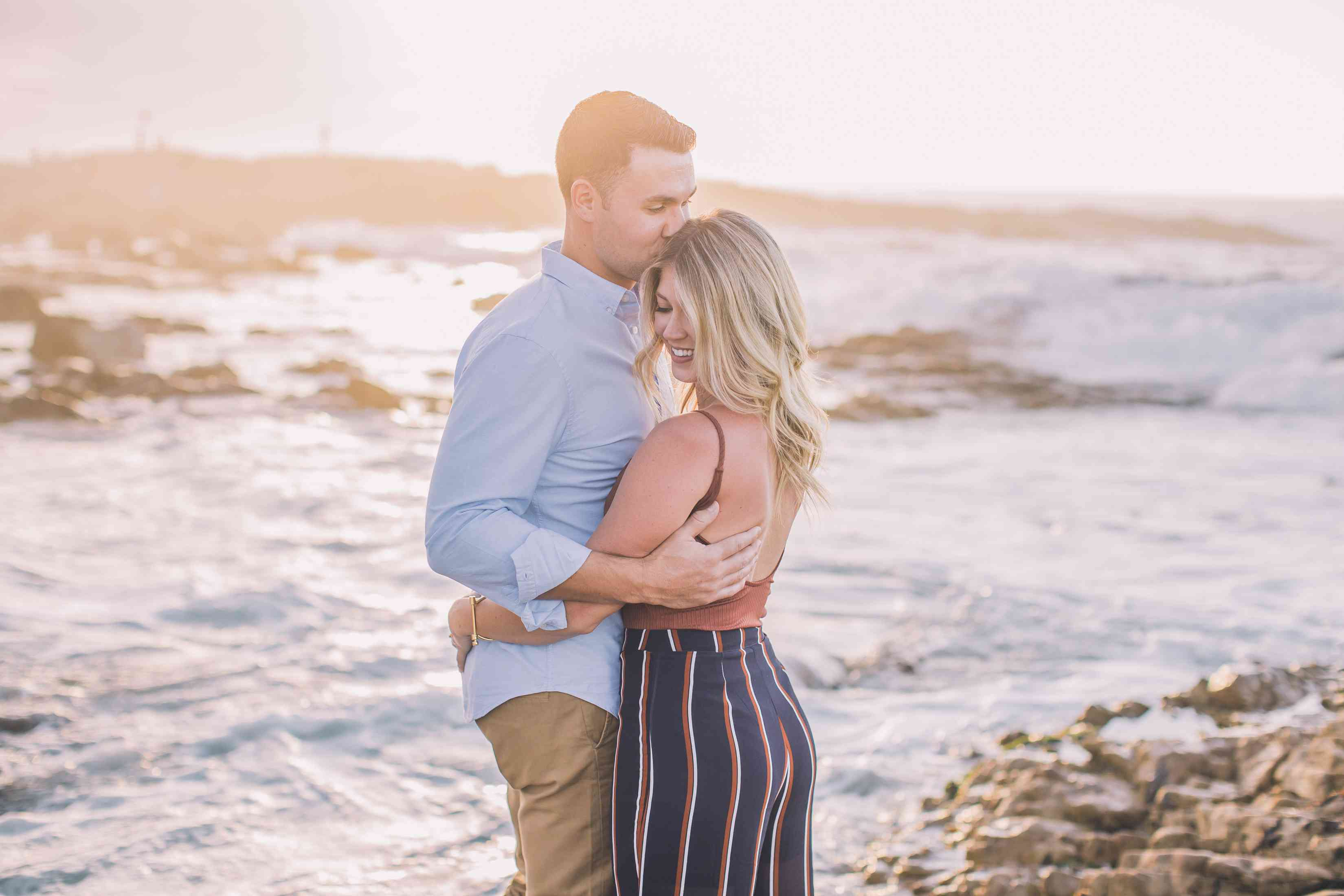 Couple hugging with ocean in the background