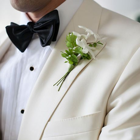 A classic white and green stephanotis boutonniere created by Wicked Willow
