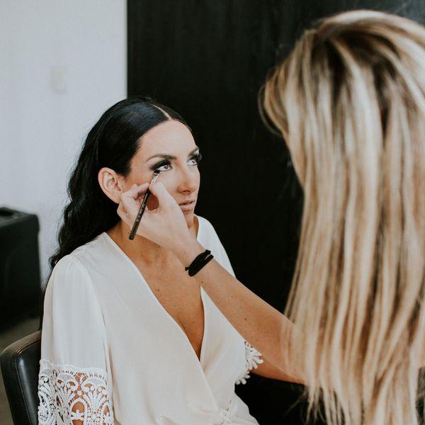 Woman applying eye makeup to a woman wearing a white robe