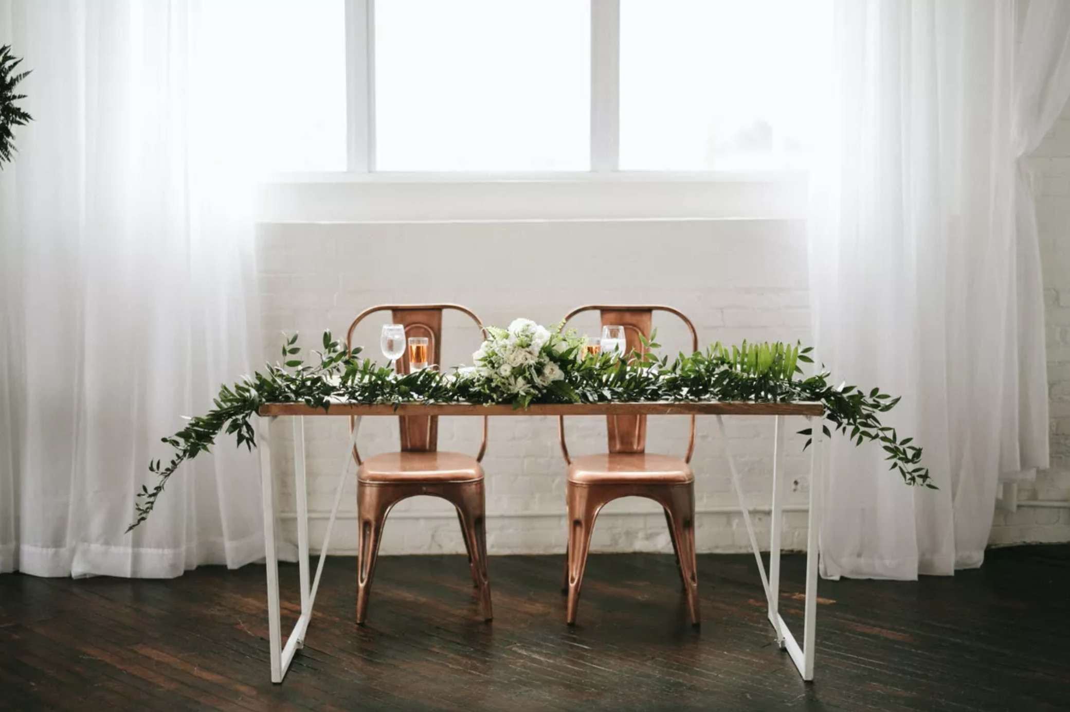 Industrial sweetheart table with copper chairs