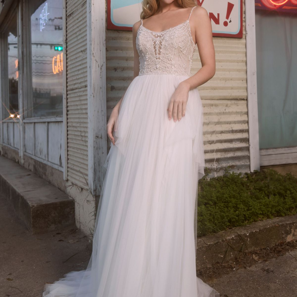Model in scoop-neck A-line gown with beaded bodice and soft net skirt with pickups