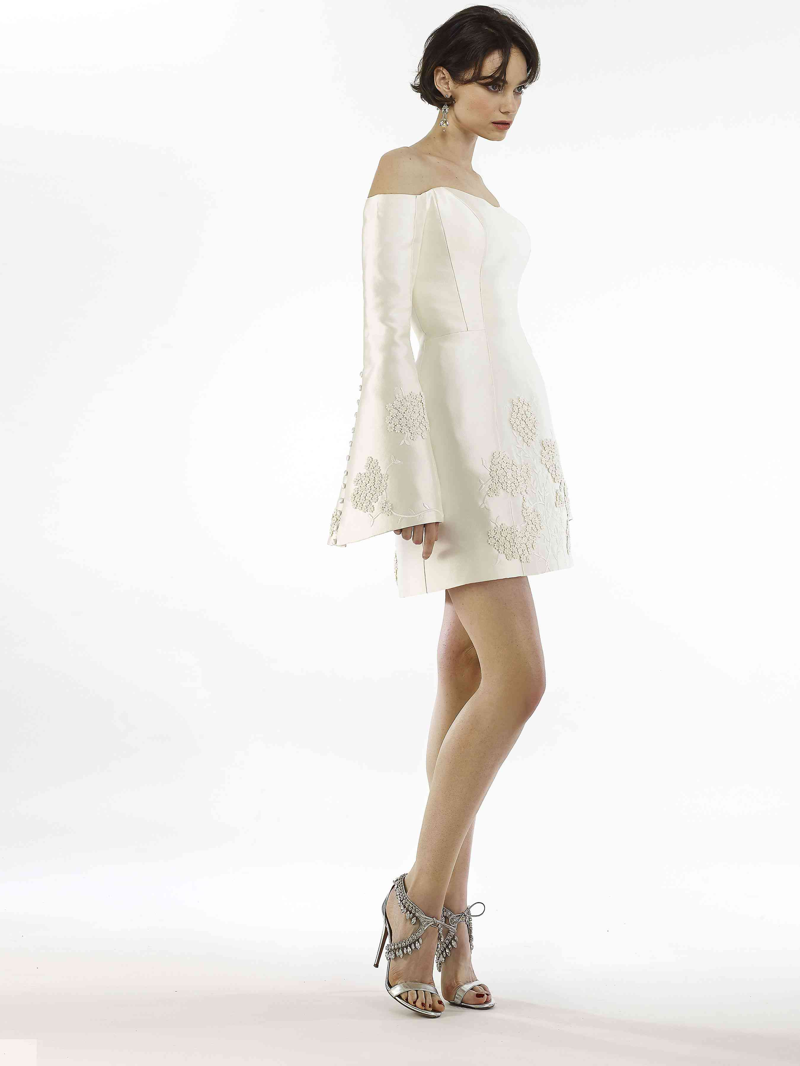 Model in embroidered off-the-shoulder mini dress with long bell sleeves
