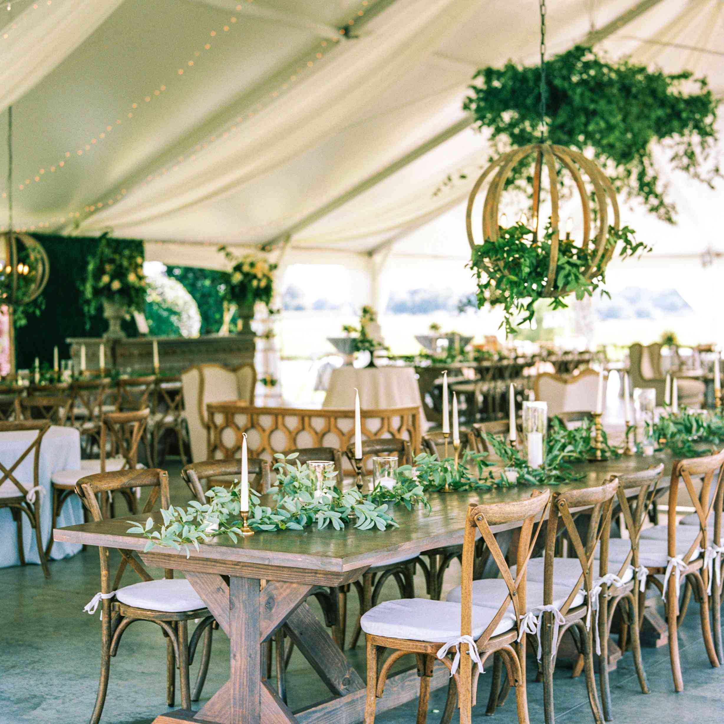 A rustic tent with greenery and natural wood