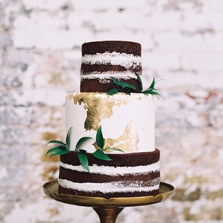A rustic chocolate wedding cake gets a touch of glam with gold foil detailing