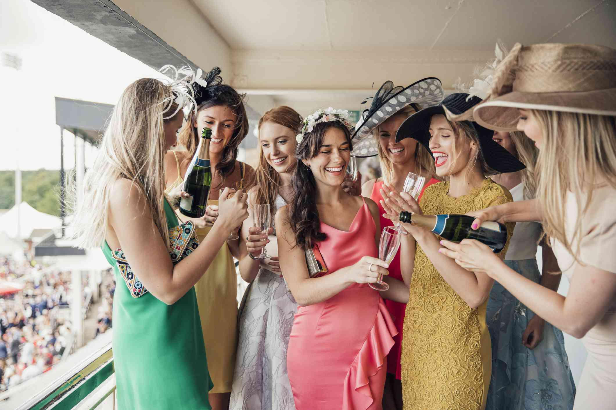 Women at a derby drinking champagne with big hats