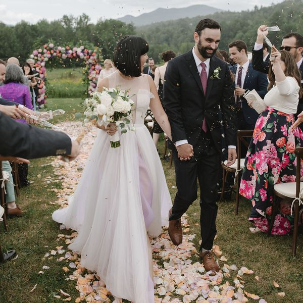 Bride and groom walking down the aisle at an outdoor wedding while guests toss flower petals